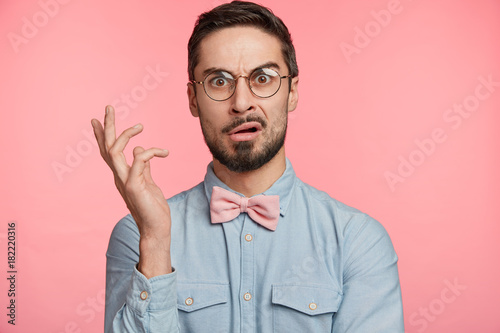 Foto Portrait of dissatisdfied man wears round spectacles, has discontet, indigant look, gestures hand, being surprised with something, poses against pink studio background