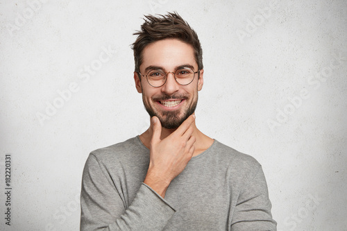 Fotografie, Obraz  Smiling male worker has trendy hairdo, keeps hand under chin, wears casual cloth