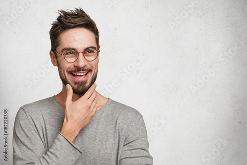 Fotografia  Positive bearded thoughtful male has brilliant idea, wants to realize it, keeps hand on chin, poses against white background with copy space for your advertismet