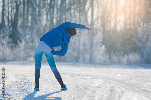 Poster Glisse hiver Runner stretching in winter Park. A healthy way of life.