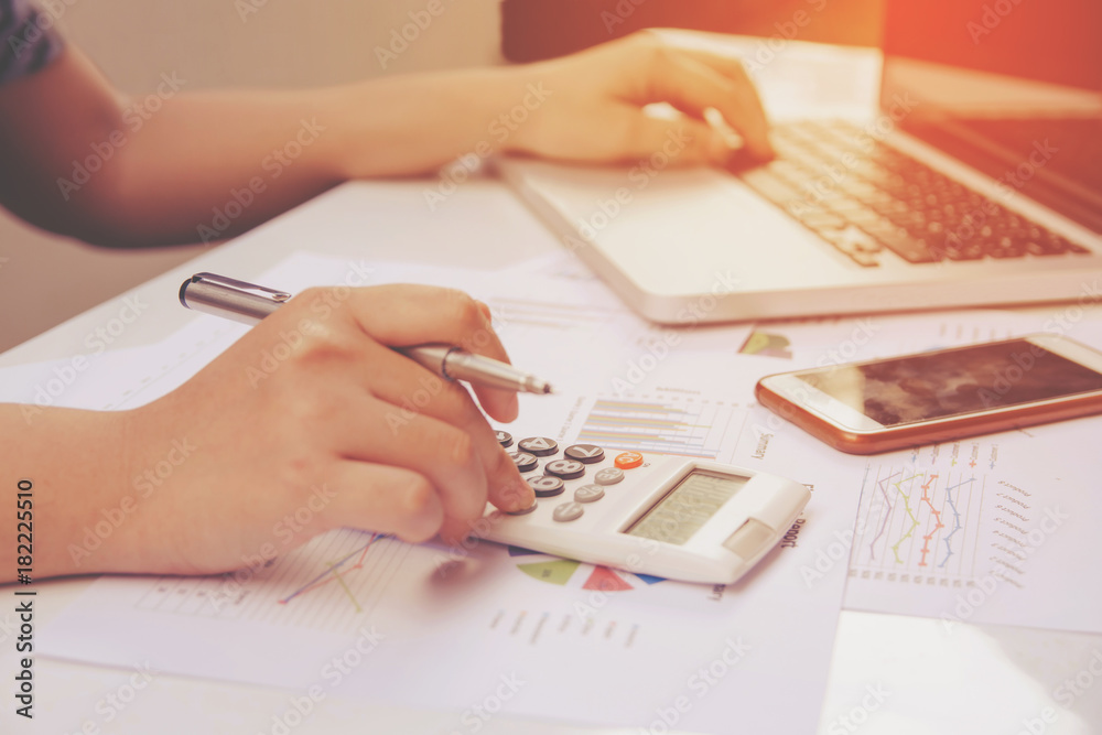 Fototapeta close up woman using calculator and laptop on paper graph data with doing finance at office.