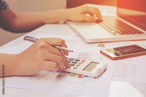 Fototapeta woman using calculator and laptop on paper graph data with doing finance at office. obraz