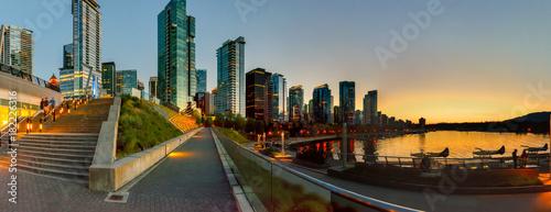 Fototapeta premium Nabrzeże dużego miasta z ogromnymi drapaczami chmur w pobliżu oceanu po zachodzie słońca