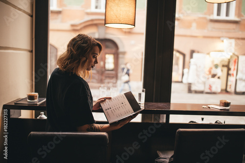 Photo Pretty girl drinking coffee and reading a menu in a bar