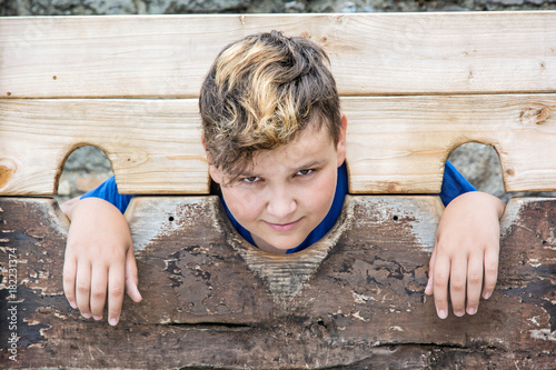 Young caucasian boy in medieval pillory Wallpaper Mural