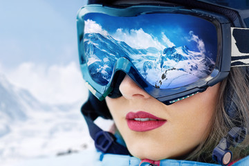 Portrait of young woman at the ski resort on the background of mountains and blue sky.A mountain range reflected in the ski mask