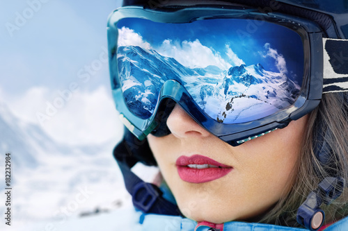 obraz dibond Portrait of young woman at the ski resort on the background of mountains and blue sky.A mountain range reflected in the ski mask