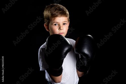 Little boxer portrait in black boxing gloves in defensive