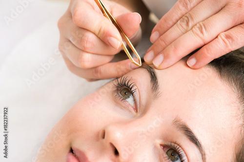Fotografering  Kosmetikstudio Augenbrauen werden von Hand mit Pinzette bei junger Frau gezupft