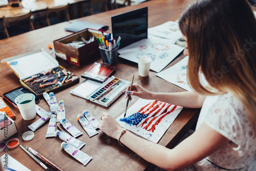 Young female illustrator drawing flag of the USA in using aquarelle paint sittin Tableau sur Toile