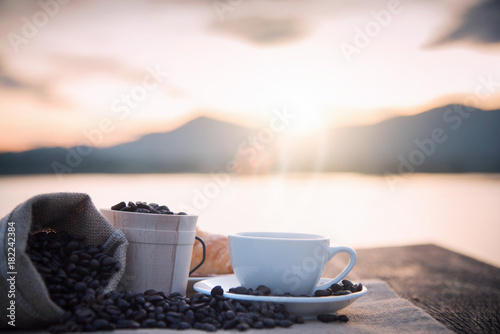 Keuken foto achterwand Cafe Coffee cup and coffee beans on wooden table in morning sunlight