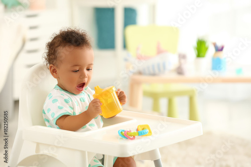 Photo  Cute baby with bottle of water sitting on chair indoors