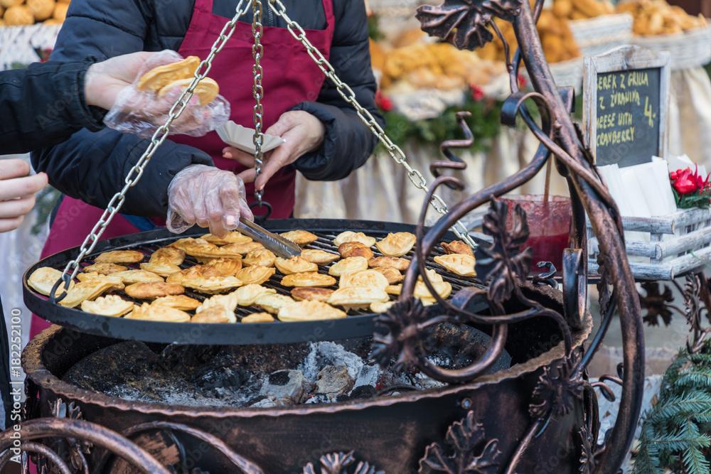 Fototapeta Traditional polish smoked cheese oscypek on Christmas market in Cracow, Poland.