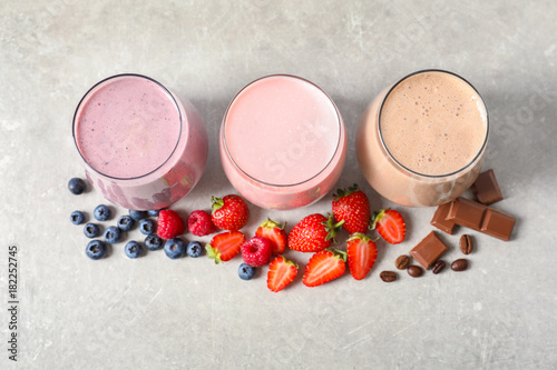 Foto op Aluminium Milkshake Glasses with different milkshakes on light background