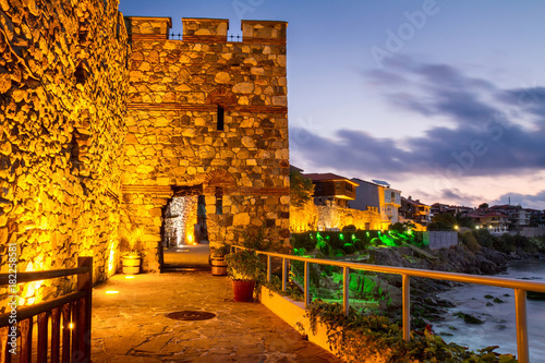 Spoed Foto op Canvas Stad aan het water Seaside sunset landscape - fortress wall and tower with illumination in the city of Sozopol on the Black Sea coast in Bulgaria