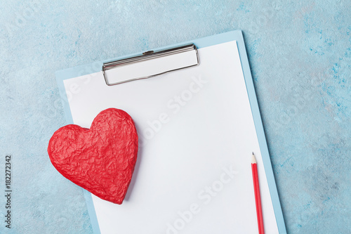 Photo Medicine clipboard and red shape of heart on blue background top view
