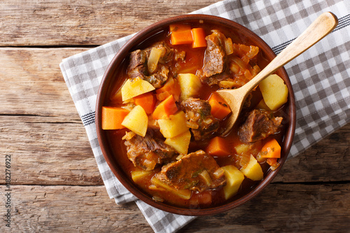 delicious stew estofado with beef and vegetables close-up. Horizontal top view