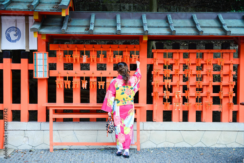 Foto op Plexiglas Bedehuis Asian woman was wearing kimono is looking at small torii charm and smiling inside Fujimi Inari temple in Kyoto, Japan.