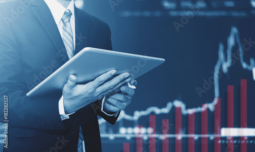 Fotografía  Businessman using digital tablet, raising graph background