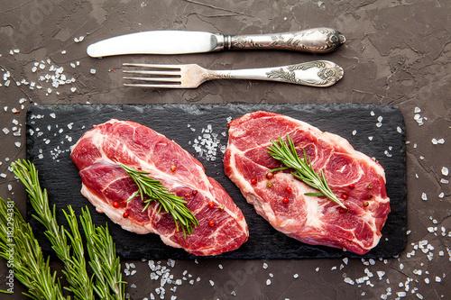 Fotografie, Obraz  Raw fresh marbled meat. Steaks and rosemary on dark background
