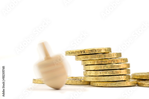 Spinning dreidel and gelt coins. Drop shadow. Isolated on white background. Copy space.