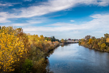 River View With Trees In Autumn Colors On Both Banks. A Bridge Is Crossing The River In The Distance. A Blue Sky With Clouds Is In The Background. The Water Is Reflecting The Blue Sky And White Clouds