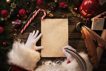 Close Up Of Santa Claus Hands Writing Letter On Wooden Desk With Copy Space