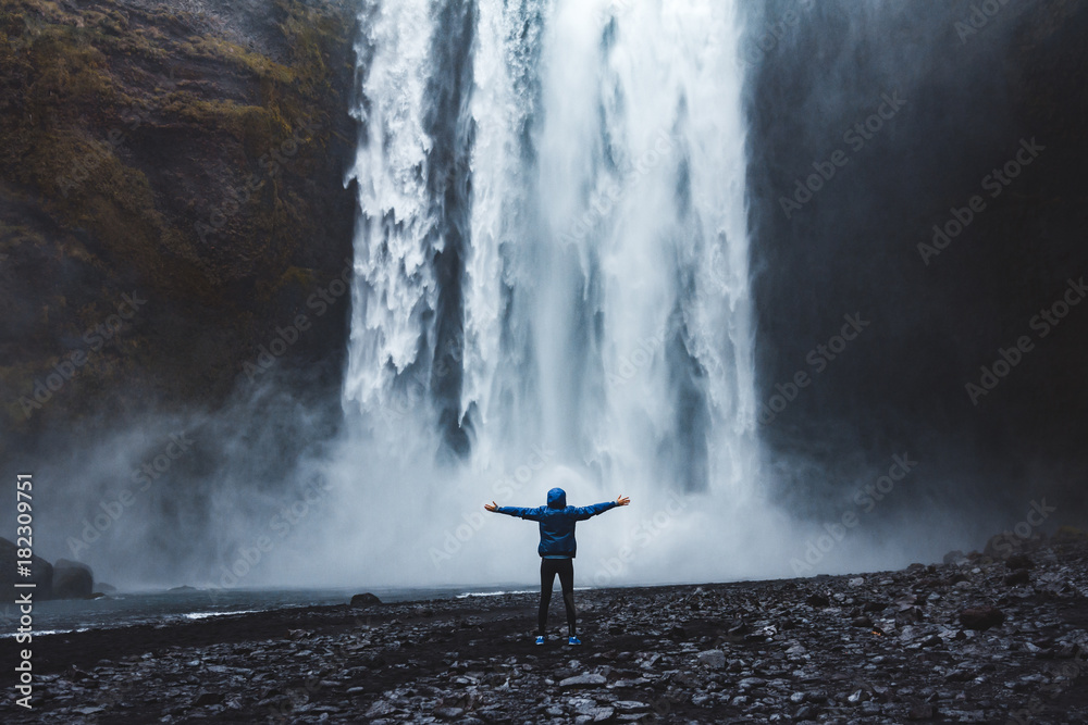 Fototapety, obrazy: A person admirnig the beauty of Skogafoss waterfall located in Iceland