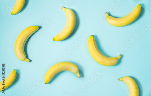 Top view of fresh yellow bananas isolated on blue background