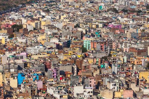 Naklejka premium Widok z lotu ptaka na chaos kolorowych budynków - stosy domów w azjatyckich miastach spowodowane dużym przeludnieniem ludzkim.