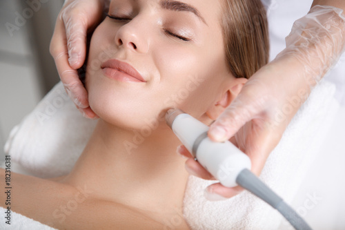 Fotografía Close up of beautician hand making ultrasound facial procedure by special equipment