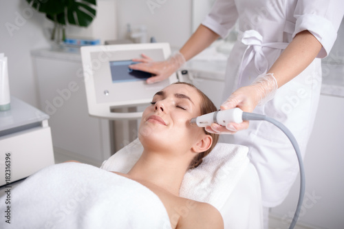 Photo  Side view of happy young woman getting cavitation rejuvenating skin treatment at spa