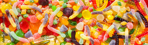 panorama close up a background from colorful sweets of sugar candies and marmalade.