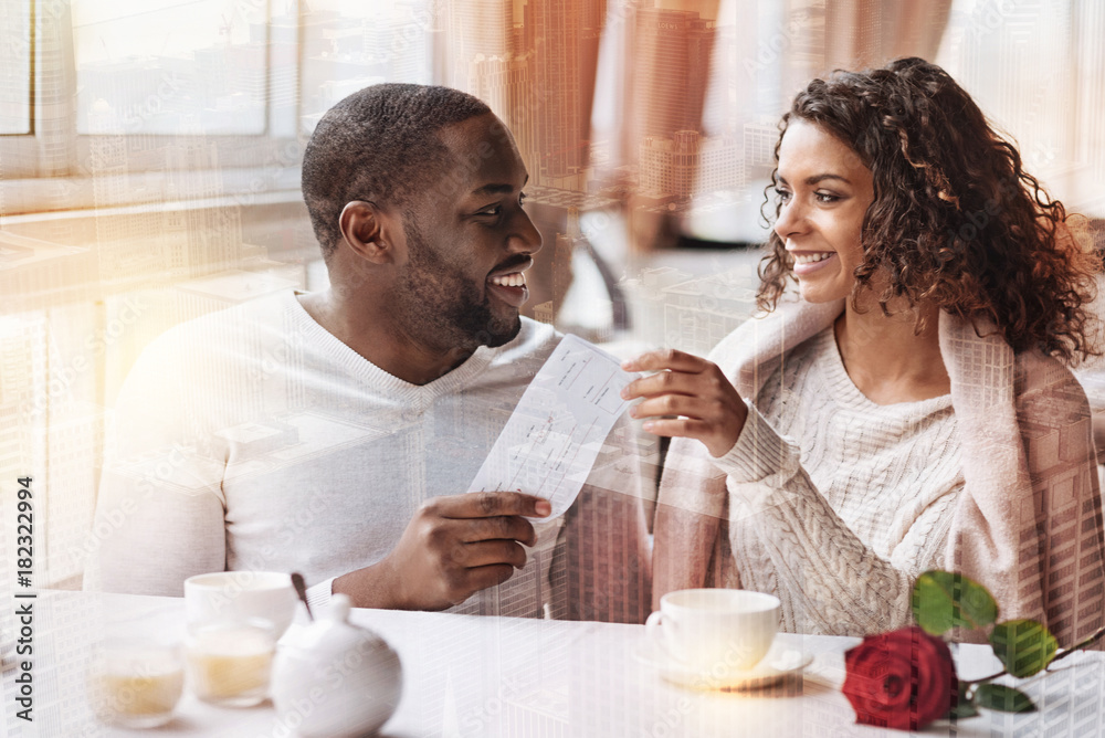 Fototapety, obrazy: Journey waiting. Positive man presenting flight tickets to his girlfriend while looking at her with love and expressing cheerful emotions