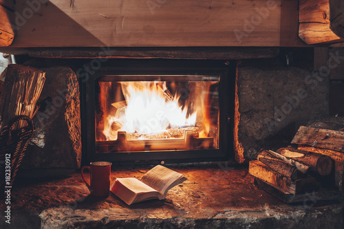 Cuadros en Lienzo Open book by the Fireplace with Christmas ornaments