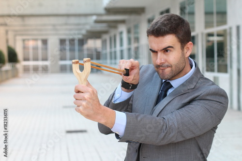Valokuva  Competitive businessman using a slingshot