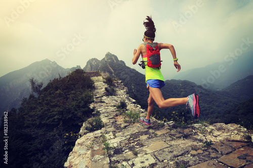 Obraz na plátně trail running woman at great wall on the top of mountain