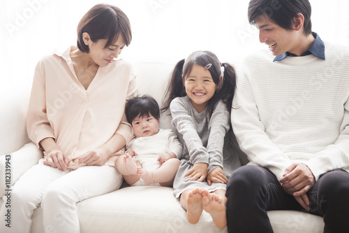 Parents, daughter and baby are sitting on the sofa and talking. Wallpaper Mural