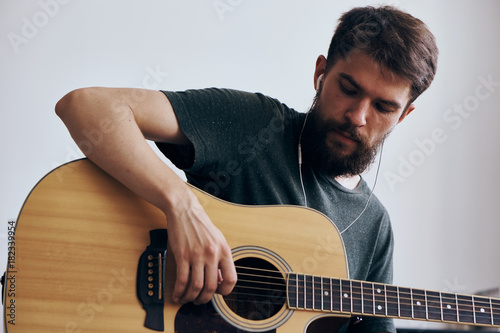 Fototapety, obrazy: Man with a beard on a white isolated background playing a guitar, musical instruments