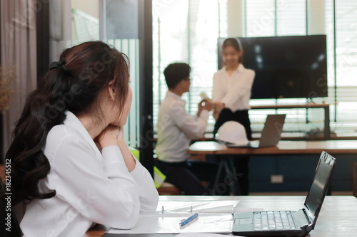 Obraz na plátně Envious angry Asian business woman looking affectionate couple in love in office