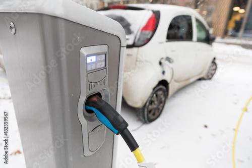 Elektroauto an Ladestation im Winter Poster