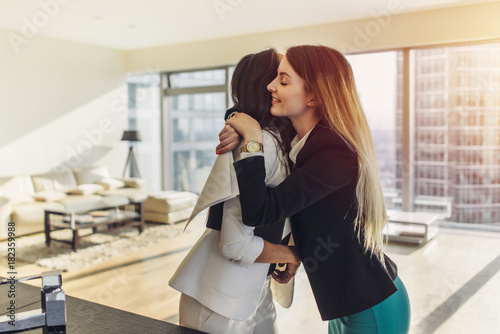 Fototapety, obrazy: Happy customer hugging her real estate agent after successful deal. Young woman purchasing a loft apartment from realtor.