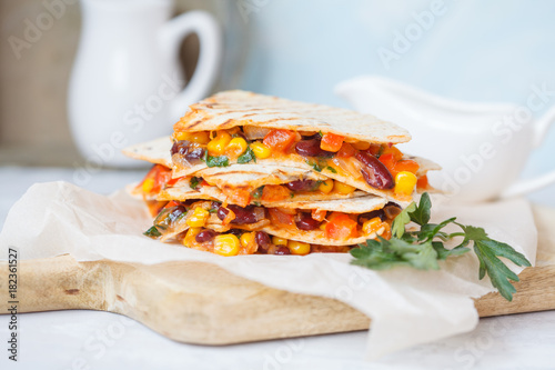 Vegetarian quesadilla with vegetables and cheese on a wooden board