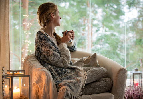 Fototapeta Young beautiful woman sitting home in the chair by the window with cup of hot coffee wearing knitted warm sweater