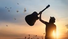 Musician Raising Guitar Over H...