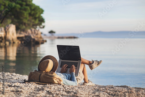 Poster Marron chocolat Young woman using laptop computer on a beach. Freelance work concept