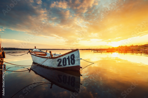 Happy New Year 2018 concept, lettering on the Boat with a reflection in the water at sunset