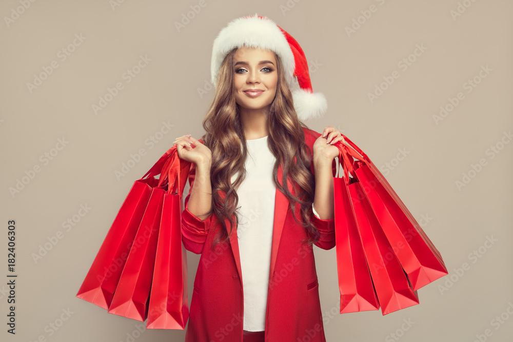 Fototapeta Portrait of cute smiling woman in santa hat. Holding red shopping bags in hands. Christmas.