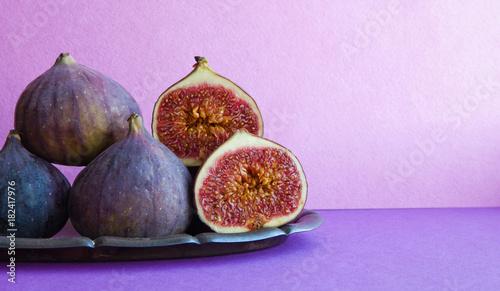 Cuadros en Lienzo Bright still life organic fig fruits on an old tray, beautiful purple violet background