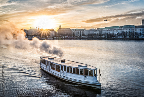 Photo steamboat on Alster Lake in Hamburg, Germany with cityscape in background during